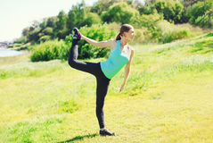 Fitness woman doing stretching exercises on grass in summer day Stock Images