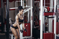 Fitness woman doing triceps exercises in the gym. Brunette fitness girl in black sport wear with perfect body in gym exercising Stock Photos