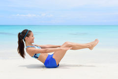 Fitness woman doing v-up crunch ab toning exercise. Fitness woman on beach with toned in shape body body doing v-up crunch ab toning exercise workout as part of stock images