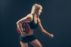 Fitness woman doing  weight training by lifting a Stock Images