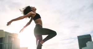 Fitness woman doing work out on rooftop stock photo