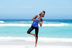 Fitness woman doing yoga exercise at beach Stock Photo