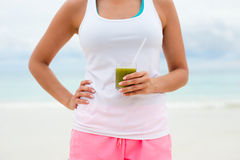 Fitness woman drinking detox smoothie at the beach Royalty Free Stock Images