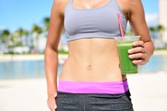 Fitness woman drinking green vegetable smoothie royalty free stock photos