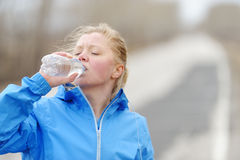 Fitness woman drinking water after beach running. Royalty Free Stock Photo