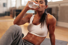 Fitness woman drinking water from bottle at gym stock images