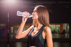 Fitness woman drinking water from bottle. Muscular young female at gym taking a break from workout. Stock Photos