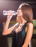 Fitness woman drinking water from bottle. Muscular young female at gym taking a break from workout. Stock Photo