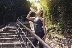 Fitness woman drinking water from a bottle after running. Workout outdoors Royalty Free Stock Photos