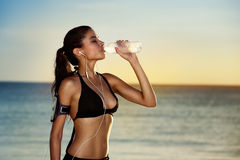 Fitness woman drinking water after exercising on summer day in b stock photos