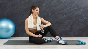 Fitness woman drinking water at gym on grey background stock photography