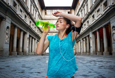Fitness woman is drinking water while outdoors training. Now it is time to invest in your body and no matter you are at hometown or traveling. Fitness woman is Stock Photos