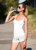 Fitness woman drinking water. After running Stock Photos