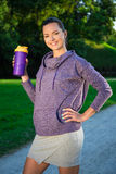 Fitness woman drinking water after running in park. Fitness woman drinking water after running in evening park Royalty Free Stock Photography