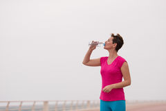 Fitness woman drinking water. After running at the promenade by the sea. Thirsty sport runner resting taking a break with water bottle drink outside after Royalty Free Stock Photo