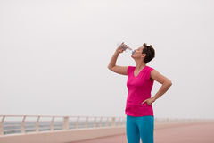 Fitness woman drinking water. After running at the promenade by the sea. Thirsty sport runner resting taking a break with water bottle drink outside after Royalty Free Stock Images
