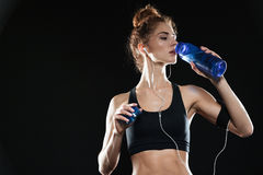 Fitness woman drinking water. In studio over black background Stock Photo