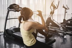 Fitness woman drinking water after work out. Exercising at gym Royalty Free Stock Images