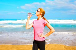 Fitness woman drinks water from bottle on the beach Royalty Free Stock Images