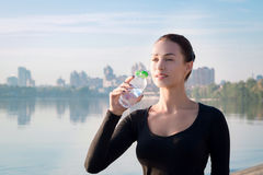 Fitness woman drinks water at morning river and city backround Royalty Free Stock Images