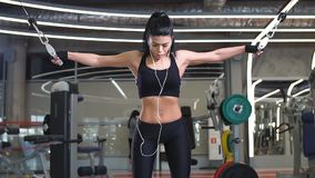 Fitness woman execute exercise with exercise-machine Cable Crossover in gym. Girl in sportswear working out and training shoulders with exercise machine stock video