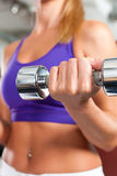 Fitness - woman is exercising with barbell in gym Stock Image