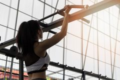 Fitness woman exercising on chin-up bar. Athlete girl doing chin-ups training royalty free stock photography