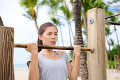 Fitness woman exercising on chin-up bar. Lady doing chin-ups training toned arms portrait outside on beach in summer Royalty Free Stock Images