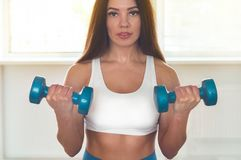 Fitness woman exercising cross fit holding dumbbells. Fitness instructor in the sport room background stock photography