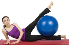 Fitness woman exercising her legs with a pilates ball Royalty Free Stock Image