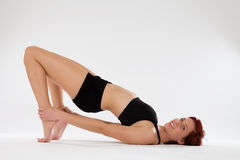 Fitness woman exercising holding her ankles Stock Photography