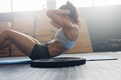 Fitness woman exercising to improve core muscle strength. Side view of fit young woman doing pilates, working on abdominal muscles. Fitness woman exercising to Stock Image
