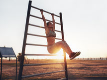Fitness woman exercising on wall bars outdoors. Portrait of strong young woman hanging on wall bars with her legs up. Fitness woman performing hanging leg raises royalty free stock image