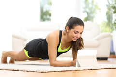 Fitness woman exercising watching fitness videos stock photo