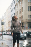 Fitness woman exposed to rain while jogging. Fitness young woman exposed to rain while jogging outdoors in the city royalty free stock photos