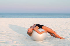 Fitness woman with fit ball on beach outdoors. Stock Images