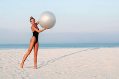 Fitness woman with fit ball on beach outdoors. Stock Image