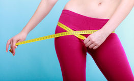 Fitness woman fit girl with measure tape measuring her loins Stock Photography