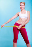 Fitness woman fit girl with measure tape measuring her loins Stock Photo