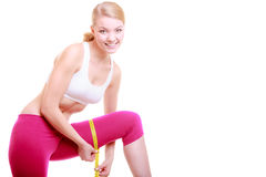 Fitness woman fit girl with measure tape measuring her thigh Stock Image