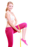 Fitness woman fit girl with measure tape measuring her thigh Stock Photography