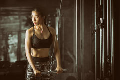 Fitness woman flexing arm muscles on cable machine at fitness center. Stock Image