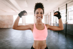 Fitness woman flexing muscles. Portrait of young fitness woman flexing muscles and smiling. African female model in sportswear showing her muscles Royalty Free Stock Photography