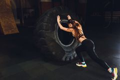 Fitness woman flipping wheel tire in gym. Fit female athlete working out with a huge tire. Back view. Sportswoman doing. An strength exercise training royalty free stock image