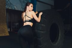 Fitness woman flipping wheel tire in gym. Fit female athlete working out with a huge tire. Back view. Sportswoman doing. An strength exercise training royalty free stock images