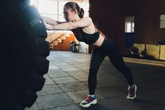 Fitness woman flipping wheel tire in gym. Fit female athlete working out with a huge tire. Back view. Sportswoman doing. An strength exercise training stock images