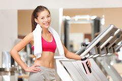 Fitness woman in gym. Portrait of fit workout girl with towel standing by treadmills in fitness club. Happy smiling young multicultural fitness model Royalty Free Stock Image