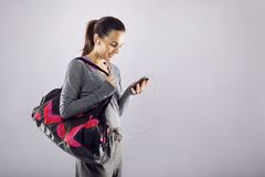 Fitness woman with gym bag listening music. Good looking female athlete with a sports bag listening to music on her mobile phone. Fitness woman in sports Stock Photography