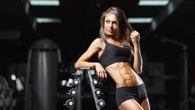 Fitness woman in the gym. Fitness woman posing in the gym. Perfect physique athletic young woman with six pack, perfect abs, shoulders and biceps Stock Photo