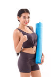 Fitness woman with hand holding yoga mat, giving thumb up Stock Photo